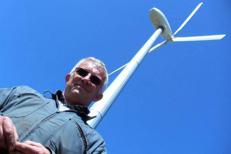 French pig and dairy farmer Gilbert Cosson with the wind turbine made by Galway-based C&F Green Energy and installed on his farm in Brittany, France.