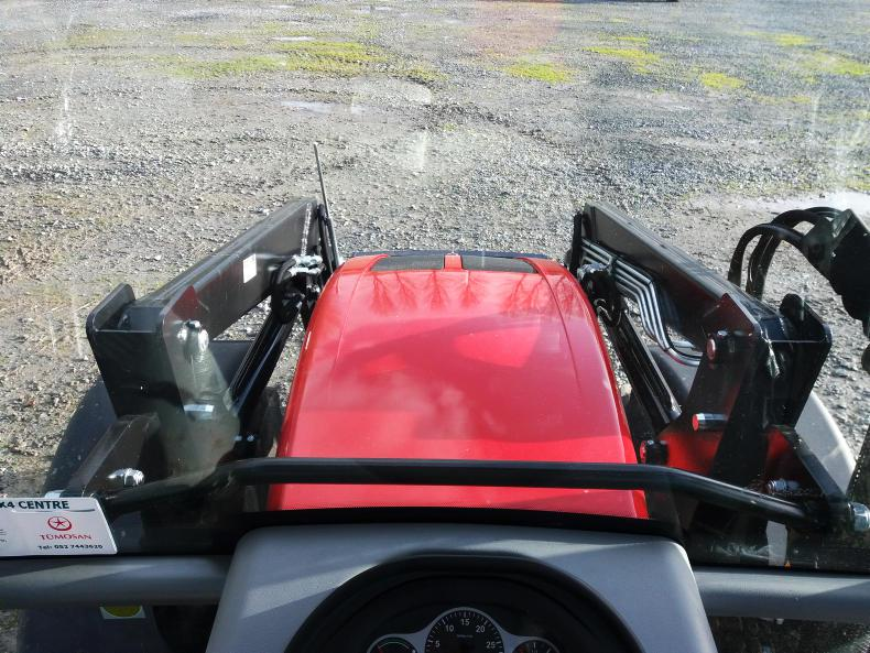 Visibility over the sloping tractor bonnet is clear. The front loader and wide mudguards obstruct the view to the wheels